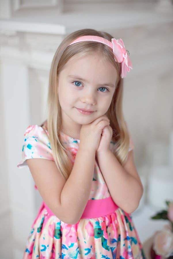 Menina doce que guarda suas mãos sob seu queixo imagens de stock