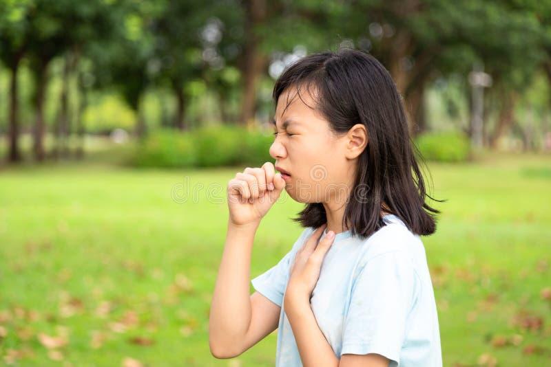 Menina doente, com dor de garganta, dor de engolir, mulher asiática com tosse, irritação e foto de stock
