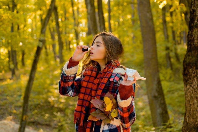 Menina doente com nariz ralo e febre Mulher com guardanapo que espirra no parque amarelo Mulher nova com lenço Mulher fotos de stock