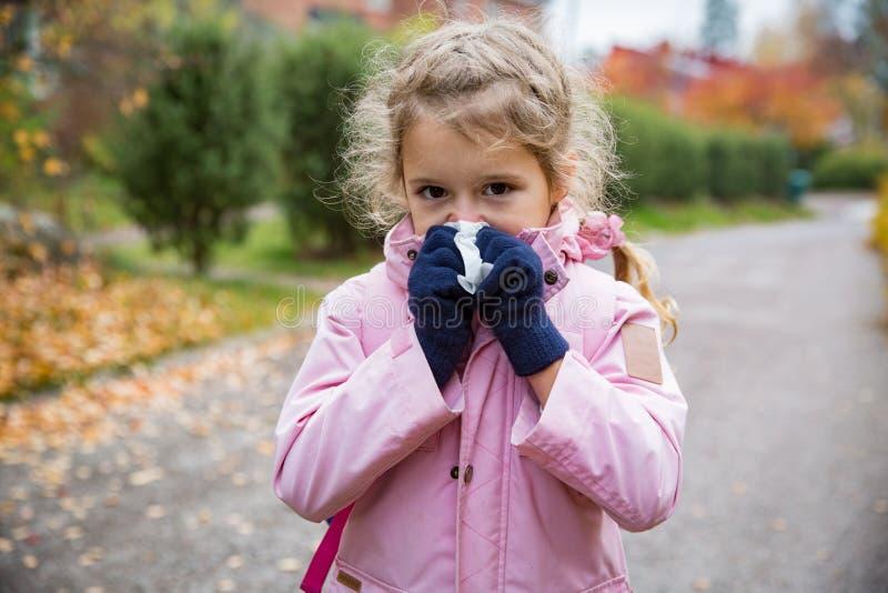 Menina doente com posição do frio e da gripe fora foto de stock
