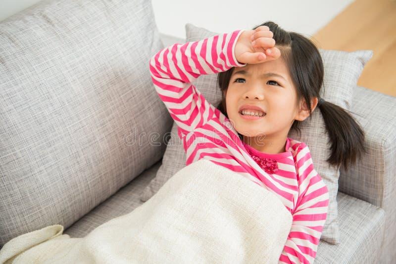 Menina doente da criança que encontra-se para baixo no sofá com febre imagem de stock royalty free