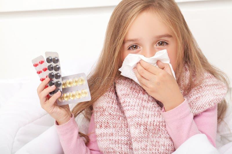 Menina doente na cama que espirra no lenço no quarto imagem de stock