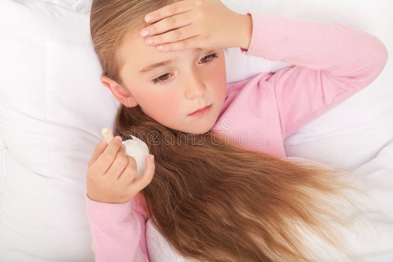 Menina doente na cama que espirra no lenço no quarto fotografia de stock royalty free