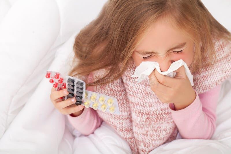 Menina doente na cama que espirra no lenço no quarto fotos de stock royalty free