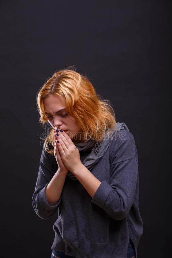 Menina doente no lenço cinzento com tosse no fundo preto imagens de stock