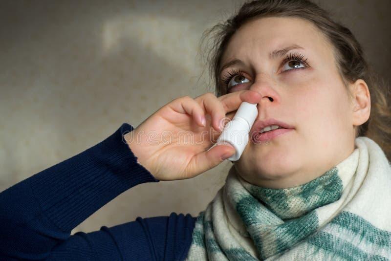 A menina doente pulveriza o pulverizador do nariz ralo na passagem nasal imagem de stock royalty free