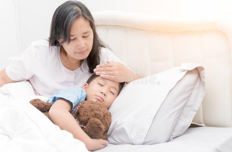 A menina doente que colocam na cama e a mãe entregam a tomada da temperatura imagens de stock