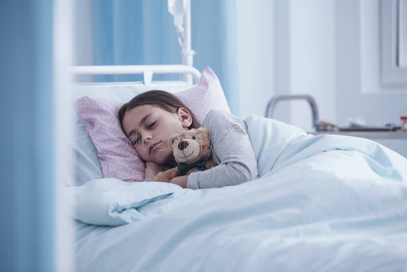 Menina doente que dorme com o urso de peluche no hospital imagem de stock royalty free