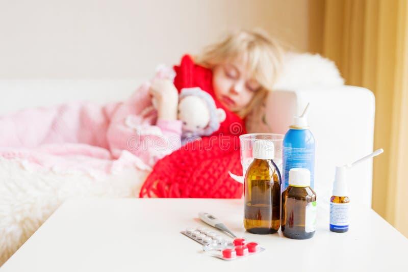 Menina doente que encontra-se na cama com as garrafas da medicina na parte dianteira imagens de stock