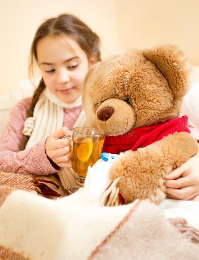 Menina doente que encontra-se na cama e que dá o chá ao urso de peluche fotografia de stock royalty free