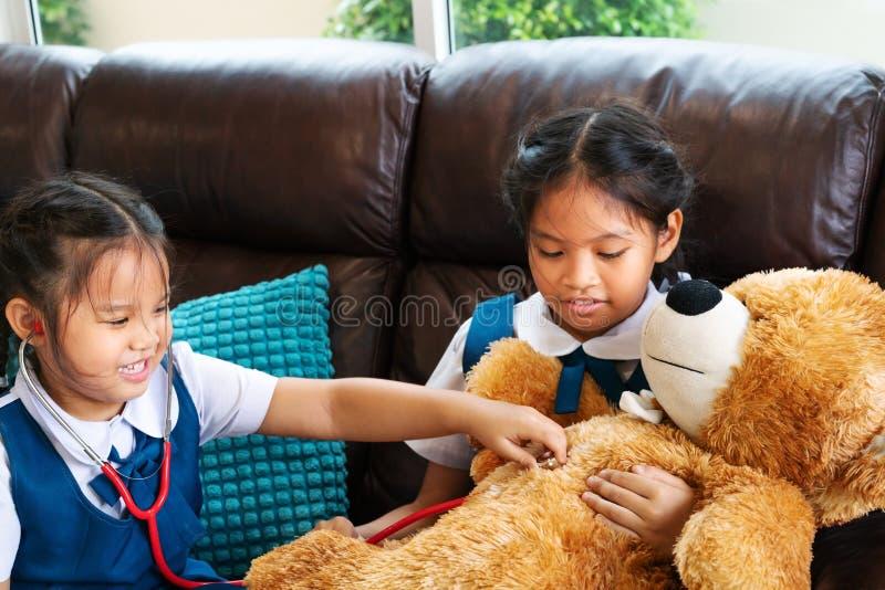 A menina dois é de sorriso e de jogo o doutor com estetoscópio Criança e conceito dos cuidados médicos fotos de stock