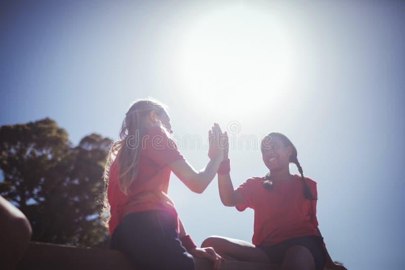 Menina dois que dá a elevação cinco entre si durante o treinamento do curso de obstáculo fotos de stock royalty free