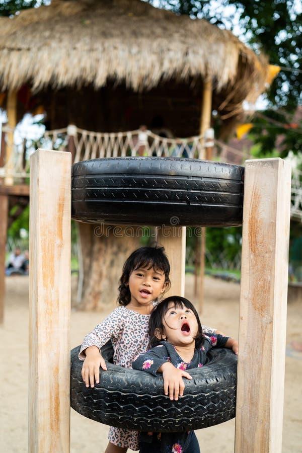 Menina dois que joga no furo do pneu no campo de jogos imagem de stock