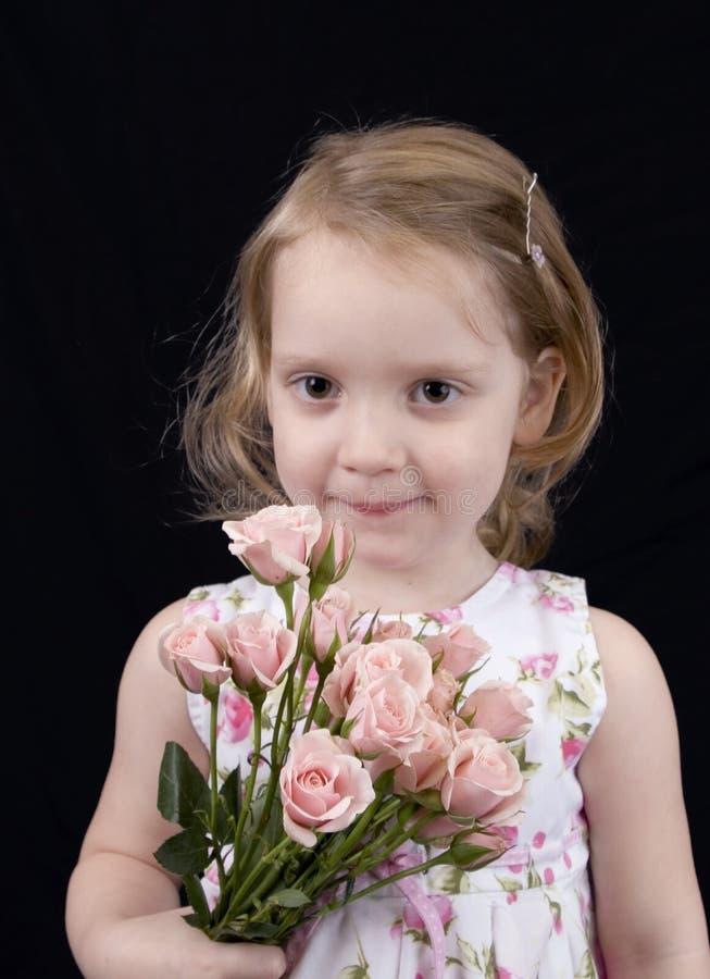 Menina dos anos de idade três com rosas imagens de stock royalty free
