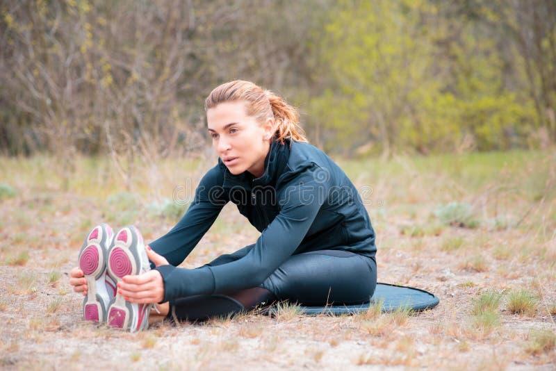 A menina dos esportes é contratada na aptidão, aquecimento imagem de stock