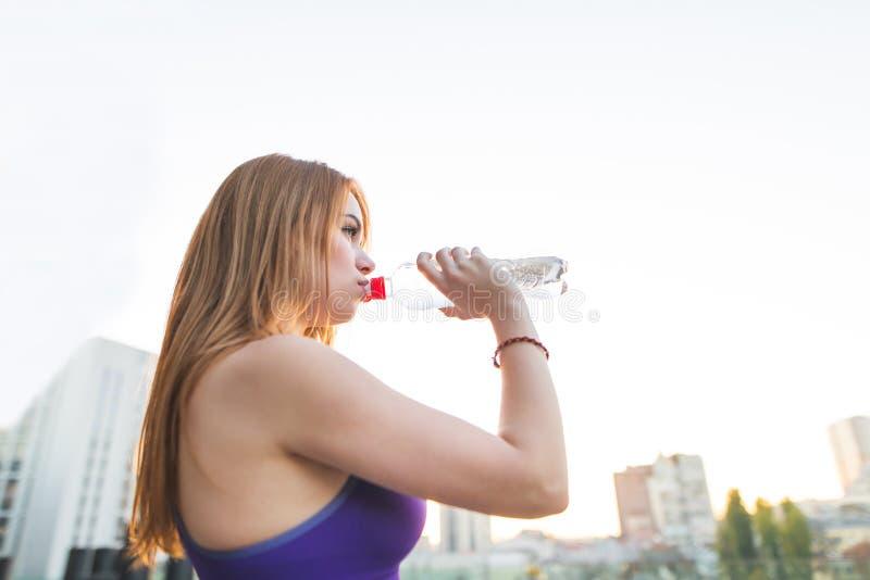 Menina dos esportes na água potável das partes superiores da garrafa na rua após ter feito esportes imagens de stock
