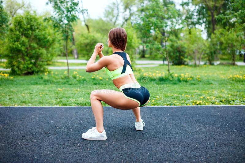 Menina dos esportes no sportswear que squatting no parque do verão imagem de stock royalty free