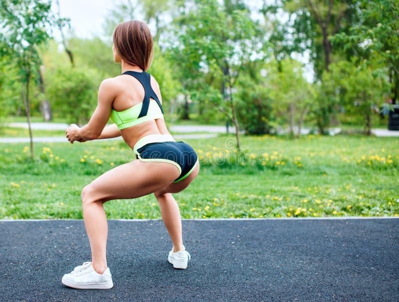 Menina dos esportes no sportswear que squatting no parque do verão foto de stock