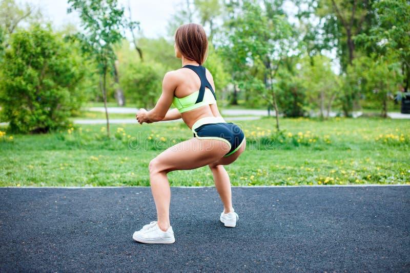 Menina dos esportes no sportswear que squatting no parque do verão fotos de stock