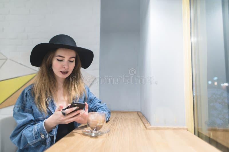 A menina dos modernos usa um smartphone em um café para um copo da bebida quente Uma mulher bebe o café em um café e usa seu tele imagem de stock