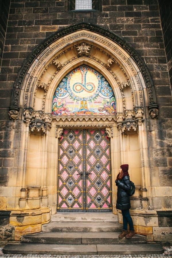 A menina dos turistas está ao lado da porta antiga bonita à catedral católica situada na cidade alta chamada imagens de stock royalty free