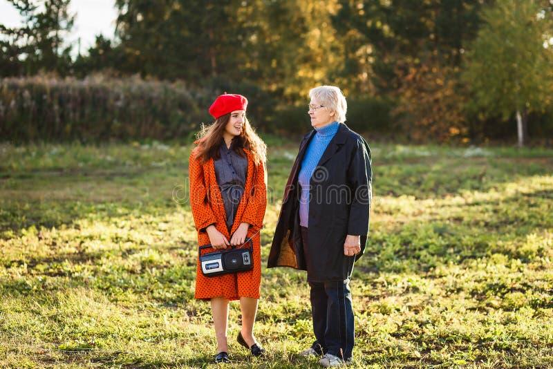 A menina e a avó adolescentes felizes falam imagens de stock