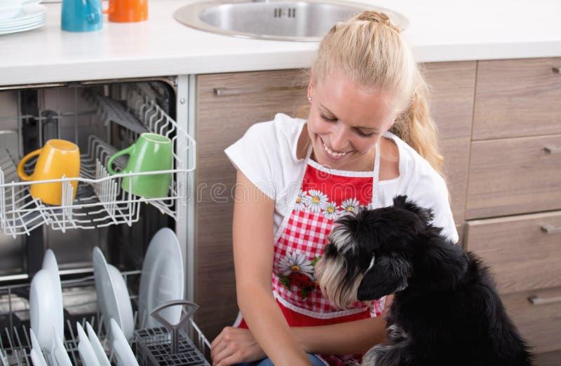 Menina e cão ao lado da máquina de lavar louça aberta foto de stock