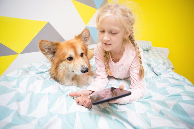 Menina e cão na cama no berçário imagem de stock