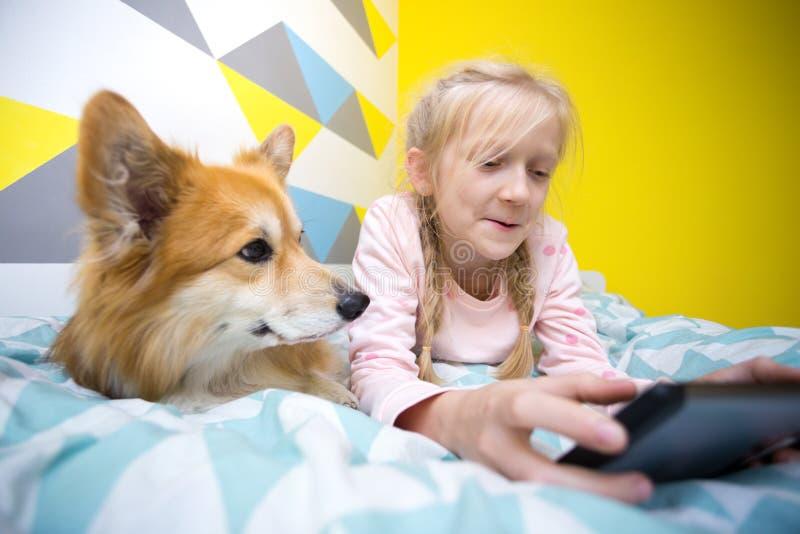 Menina e cão na cama no berçário imagem de stock royalty free
