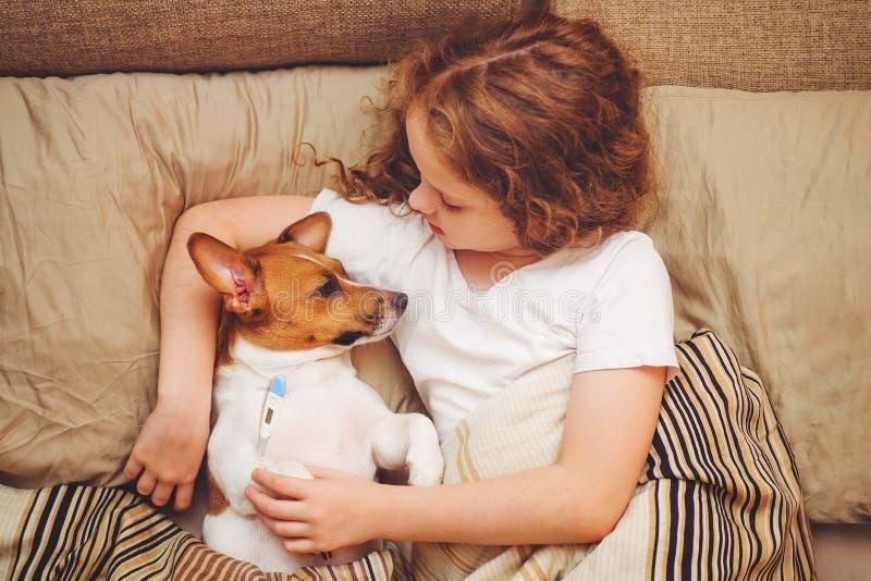 menina e cachorrinho sob a edredão com febre e temperatura foto de stock