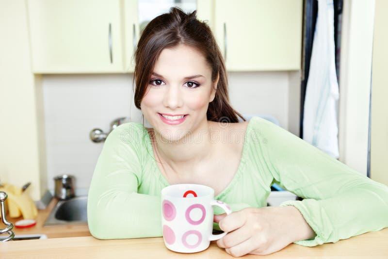 Menina e copo de chá na cozinha foto de stock