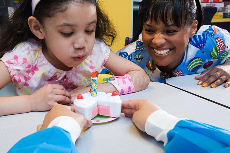 Menina e enfermeiras com o bolo de aniversário do brinquedo foto de stock royalty free