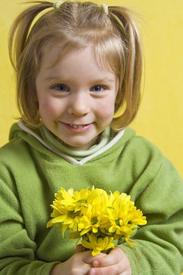 Menina e flores amarelas imagem de stock royalty free
