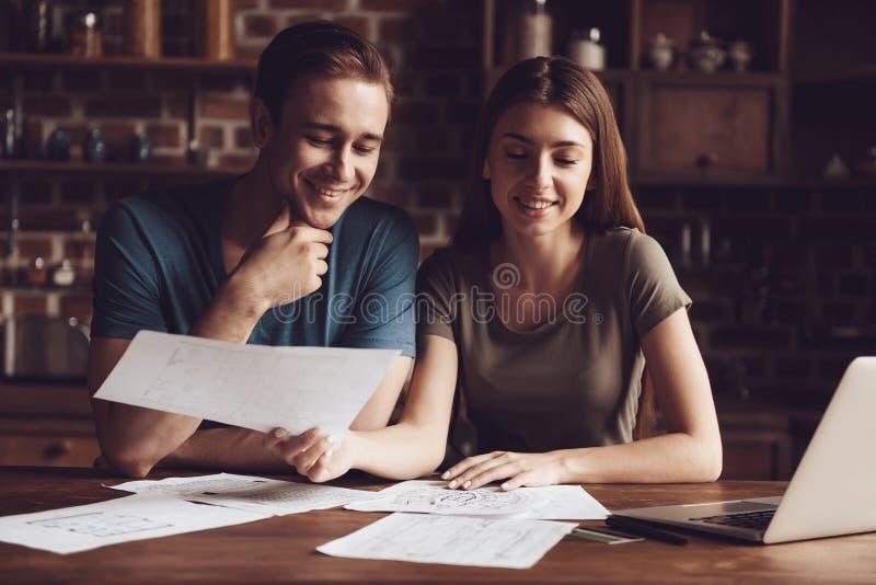Menina e Guy Working Home consideráveis com portátil fotografia de stock