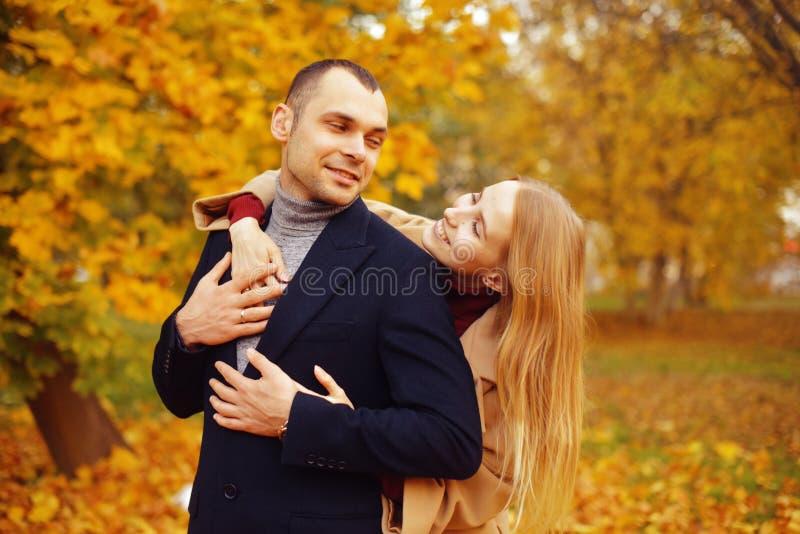 Menina e homem ou amantes no abraço da data Pares no amor no parque outono que data o conceito Homem e mulher com caras felizes fotos de stock