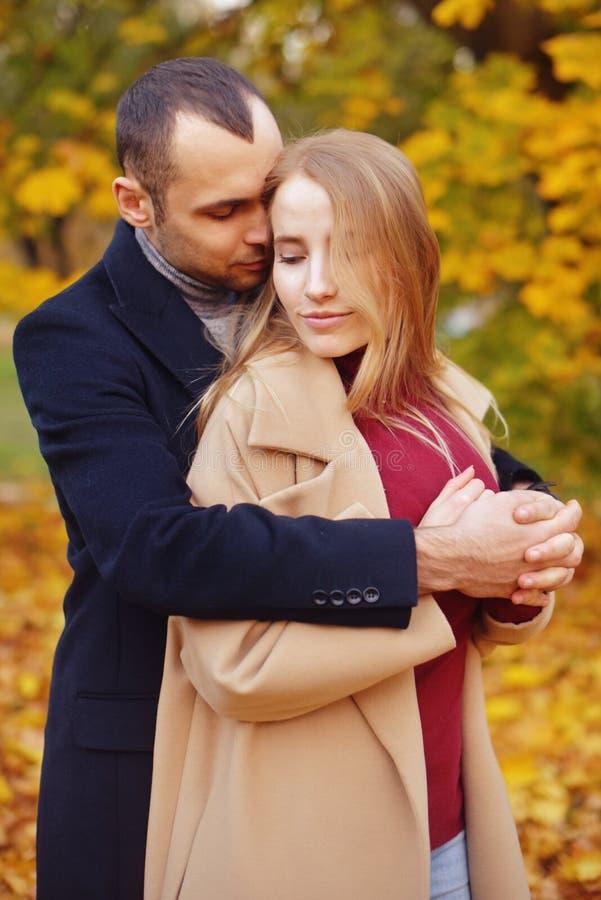 Menina e homem ou amantes no abraço da data Pares no amor no parque outono que data o conceito Homem e mulher com caras felizes fotografia de stock