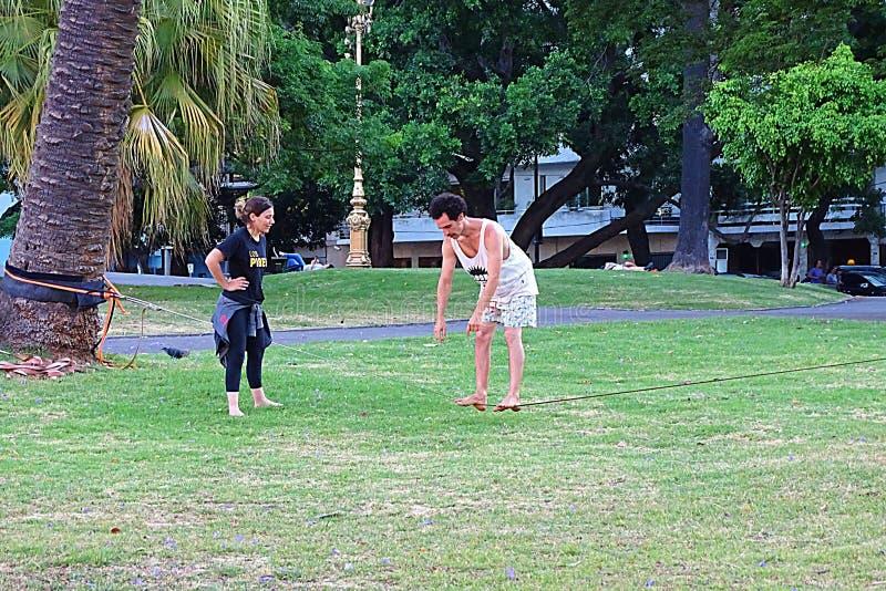 Menina e homem que fazem equilíbrios no parque imagem de stock