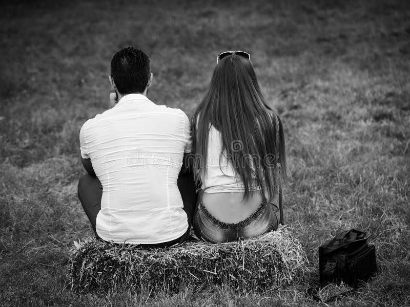 Menina e homem que sentam-se no pacote de feno na grama verde fotografia de stock