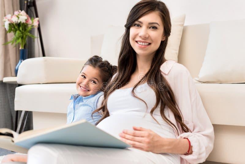 Menina e livro de leitura grávido da mãe imagem de stock