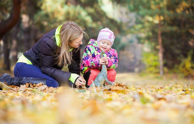 Menina e mãe que jogam com dinossauro do brinquedo fora foto de stock royalty free