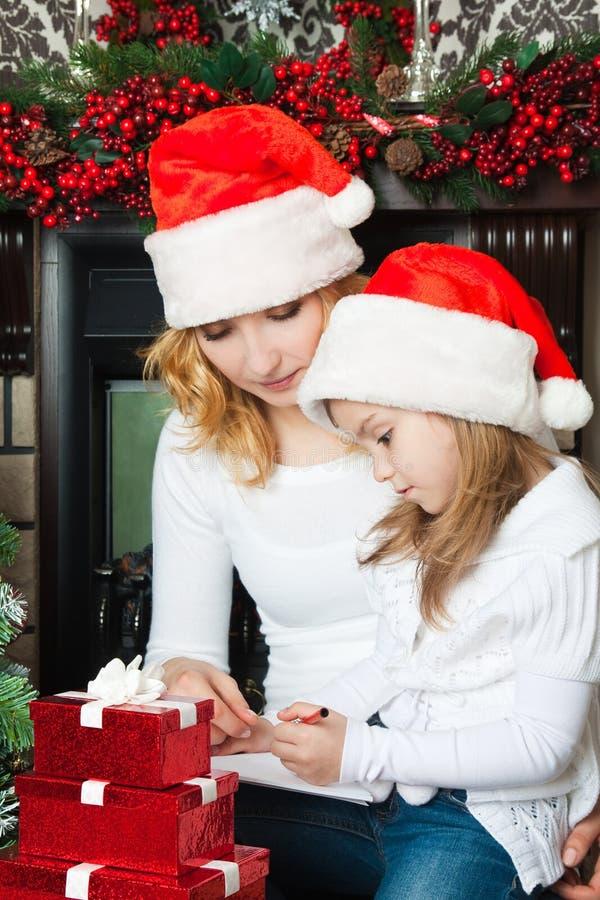 A menina e a matriz escrevem a letra a Santa imagem de stock