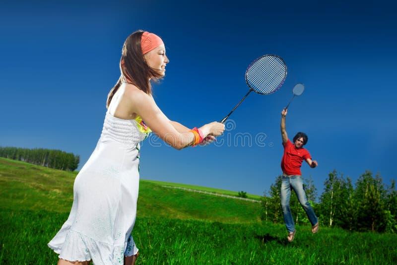 Menina e menino agradáveis com raquetes foto de stock