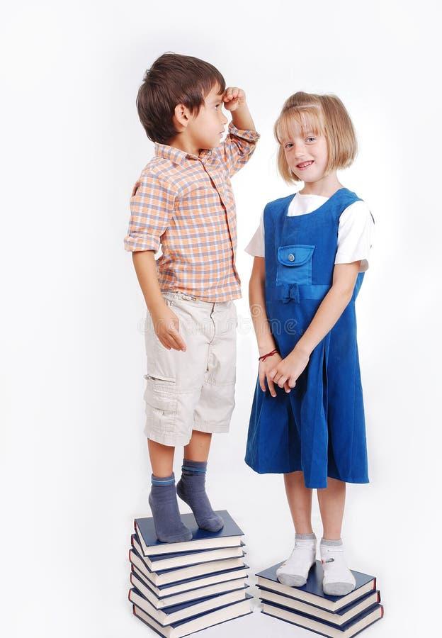 Menina e menino bonitos pequenos com muitos livros isolados imagem de stock royalty free