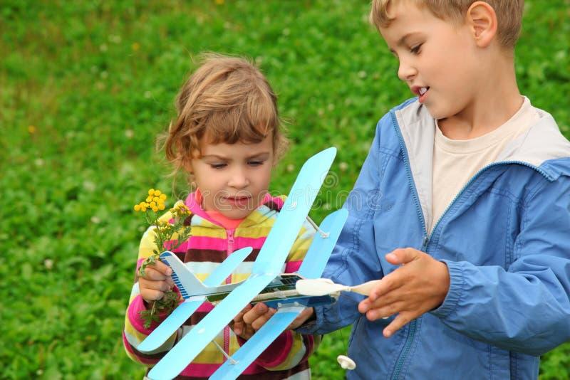 Menina e menino com o avião do brinquedo nas mãos imagem de stock