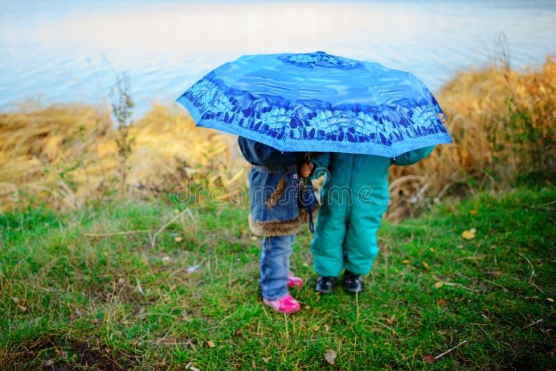 Menina e menino com o guarda-chuva que joga na chuva As crianças jogam exterior pelo tempo chuvoso na queda Divertimento do outon imagens de stock royalty free