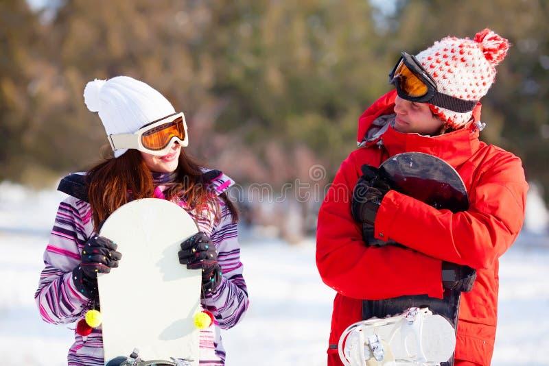 Menina e menino com snowboards imagem de stock