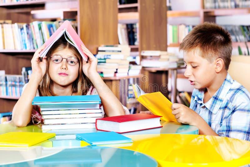Menina e menino em uma biblioteca fotografia de stock royalty free