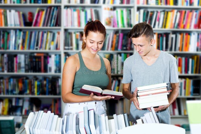 Menina e menino nas livrarias fotos de stock royalty free