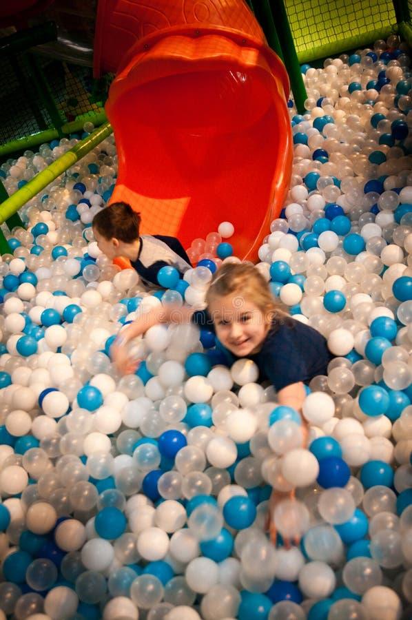 Menina e menino no parque de diversões interno do divertimento fotos de stock royalty free