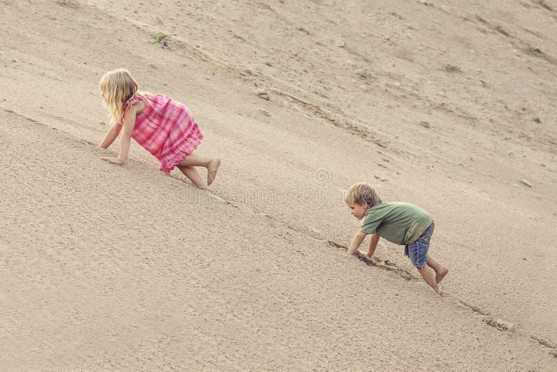 Menina e menino que escalam na duna de areia Árvore no campo fotografia de stock royalty free
